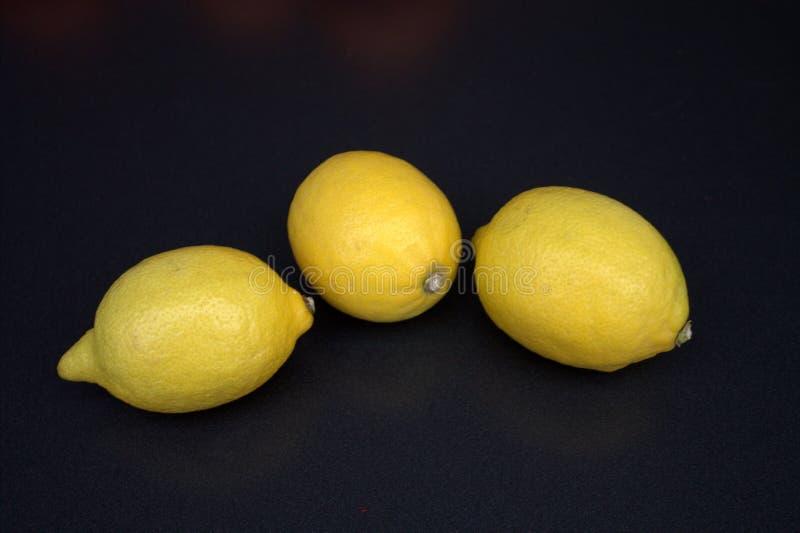 Tre gula citroner på en mörk bakgrund royaltyfri fotografi