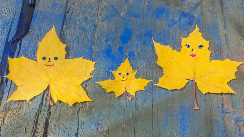 Tre gula lönnlöv med gladlynt tystar ned målat på dem ligger på en blå träyttersida fotografering för bildbyråer