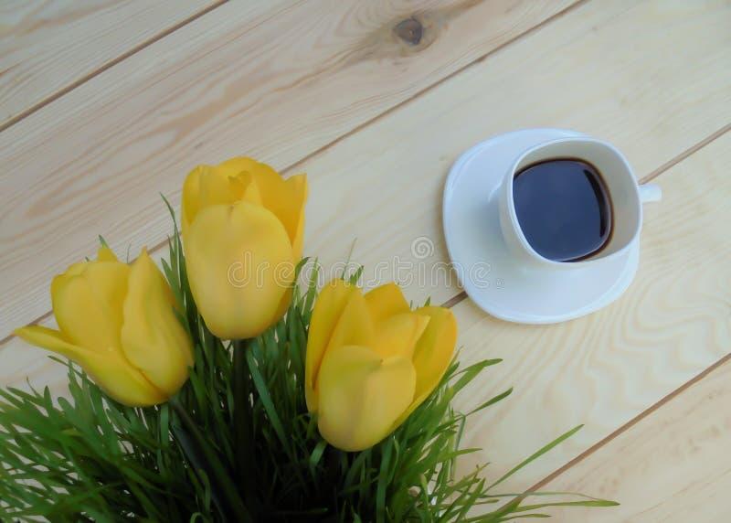 Tre gula tulpan och vit kopp för grönt gräs med kaffe på träbräden arkivbilder
