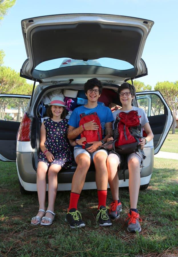 Tre gulliga barn laddar resväskor från stammen av bilen arkivbilder