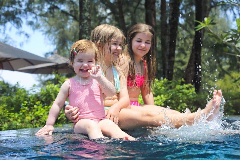 Tre gulliga flickor som spelar i simbassäng fotografering för bildbyråer