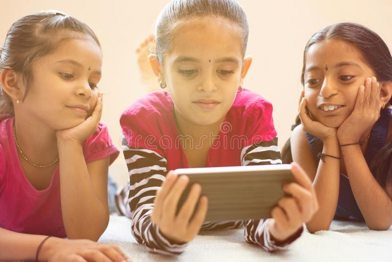Tre gulliga indiska barn som håller ögonen på barnet som använder smartphonen med smiley framsidor på säng royaltyfria bilder