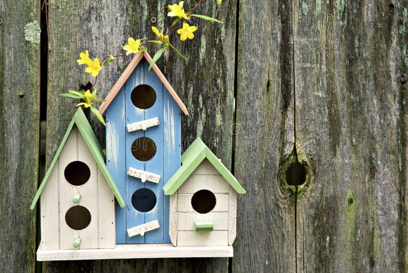 Tre gulliga lite birdhouses på trästaket med blommor arkivfoton