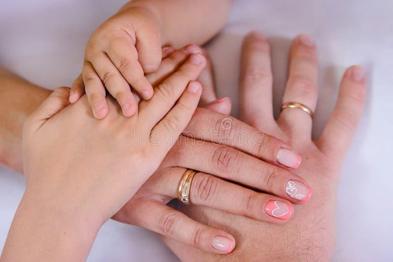 Tre händer av familjen, barnet, modern och fader Begreppet av enhet, service, skydd och lycka arkivbilder