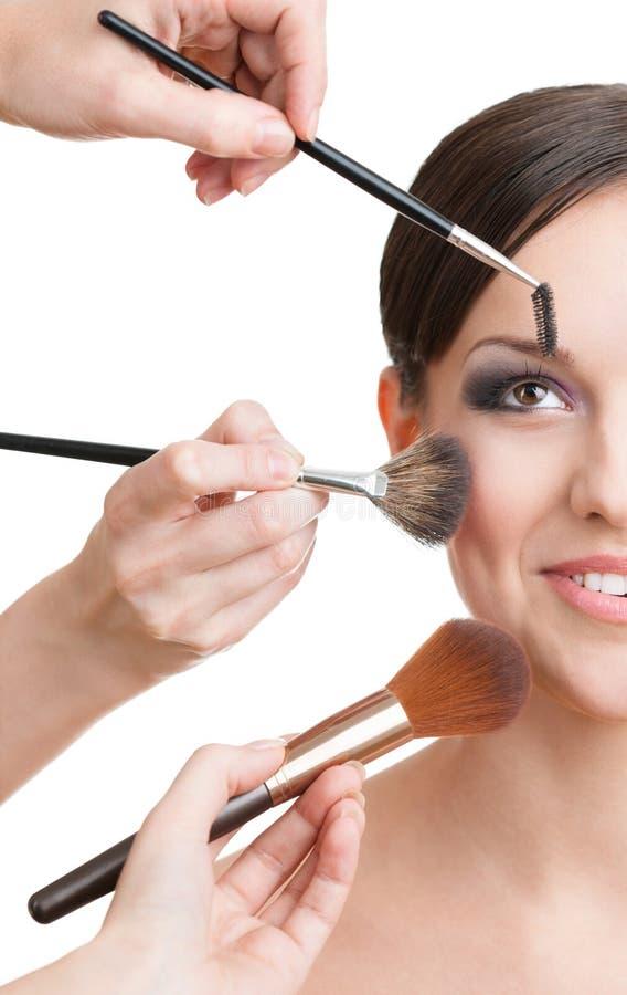 Tre händer av makeupkonstnärer som applicerar skönhetsmedel arkivbild