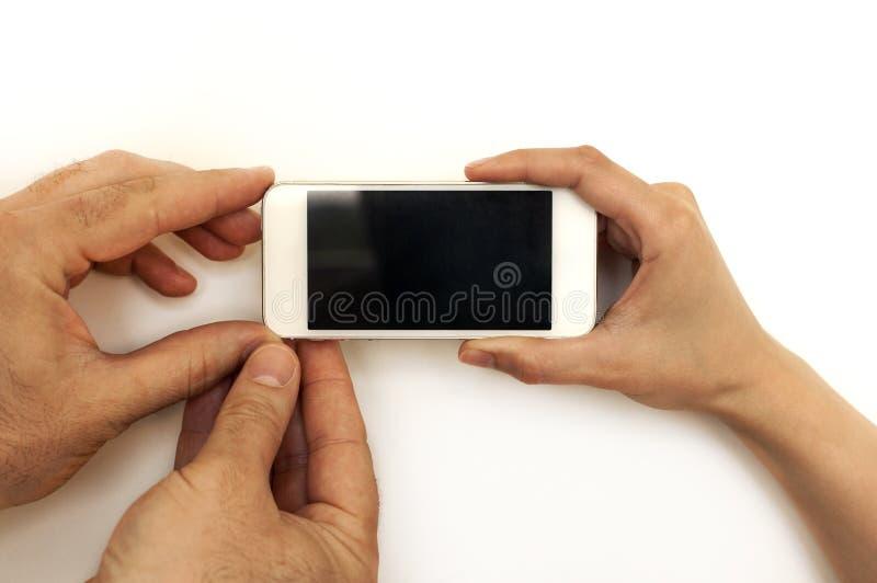 Tre händer, man och kvinnlig, hållande mobiltelefon, smartphone arkivfoton