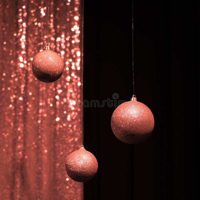 Tre hängande julbollar i färgen av att bo korall royaltyfria foton