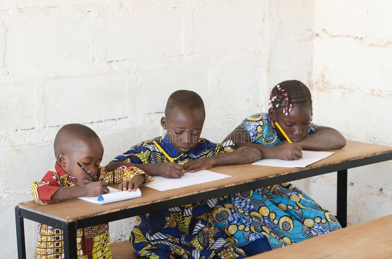 Tre härliga afrikanska barn i skolan som tar anmärkningar under C royaltyfri foto