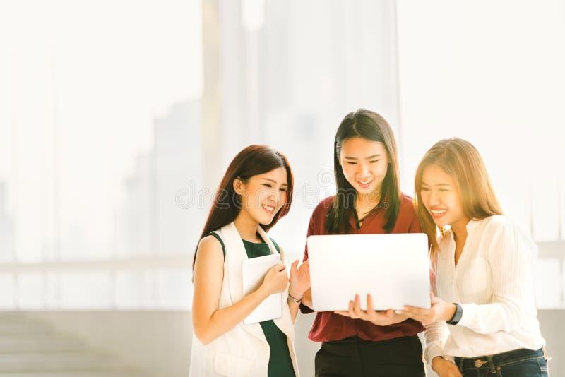 Tre härliga asiatiska flickor på tillfälligt affärsmöte med bärbar datoranteckningsboken och den digitala minnestavlan på solnedg arkivbild