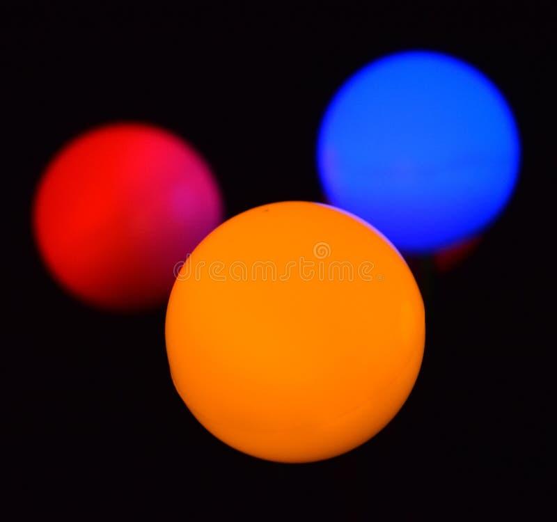 Tre härliga färgrika bollar i mörkret arkivbilder