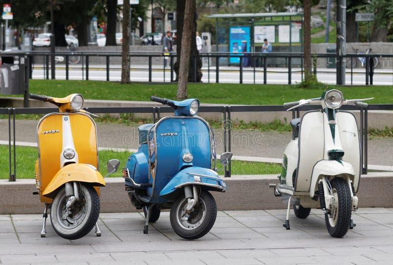 Tre härliga för blått och vita retro vespasparkcyklar för guling, parkerar royaltyfri foto