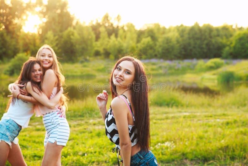 Tre härliga flickor som går och skrattar på solnedgång i parkera stående två för pelikan för kamratskap för bakgrundsbegrepp våt  arkivfoton
