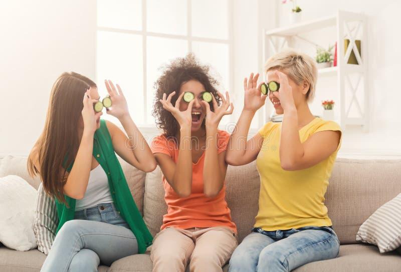 Tre härliga flickor som täcker ögon med gurkan royaltyfri bild