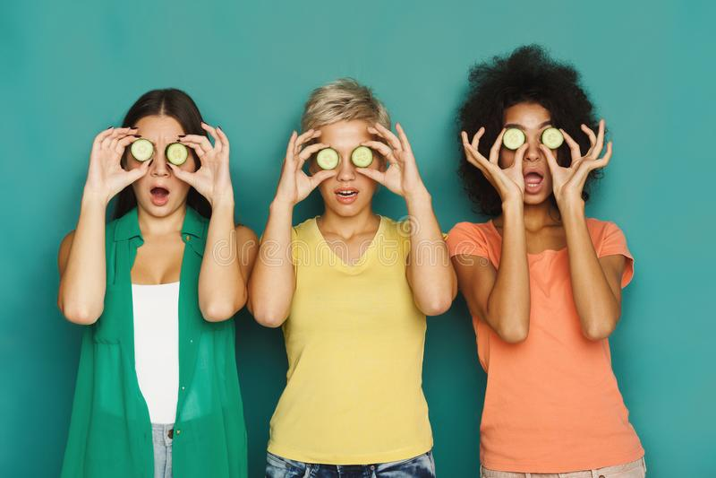 Tre härliga flickor som täcker ögon med gurkastycken royaltyfria foton