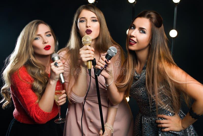Tre härliga kvinnor för ung smiley i karaoke royaltyfri foto