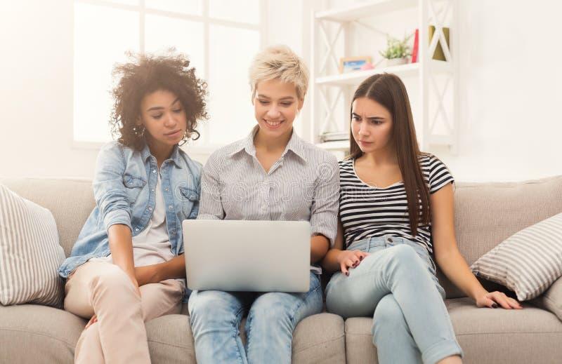 Tre härliga kvinnor som hemma använder bärbara datorn arkivfoto