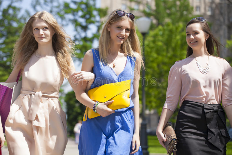 Tre härliga modekvinnor som går på gatan royaltyfria bilder