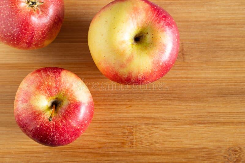 tre härliga röd-guling äpplen ligger på en trätriangelbakgrund i hörnet fotografering för bildbyråer