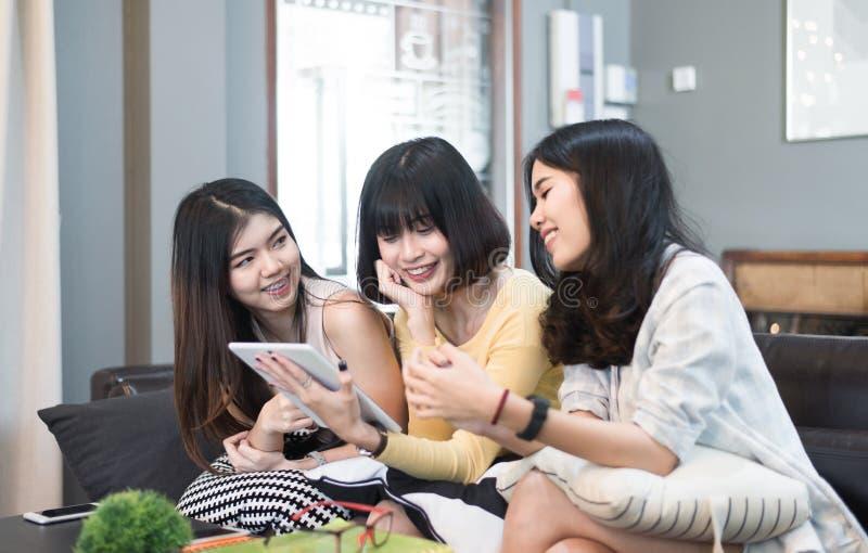 Tre härliga unga asiatiska kvinnavänner som använder talande le för minnestavladator och tillsammans skrattar royaltyfria bilder