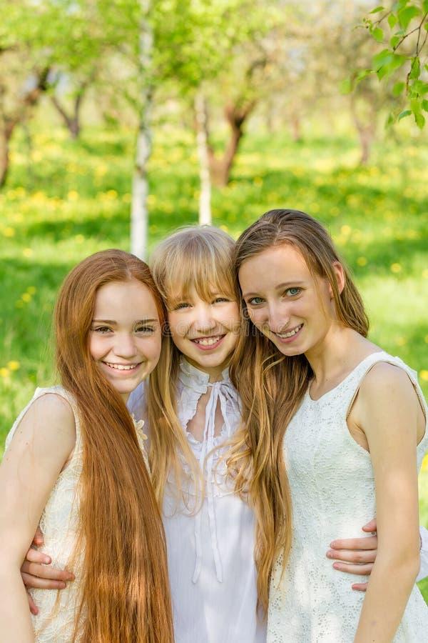Tre härliga unga flickor i vita klänningar i sommar royaltyfri bild
