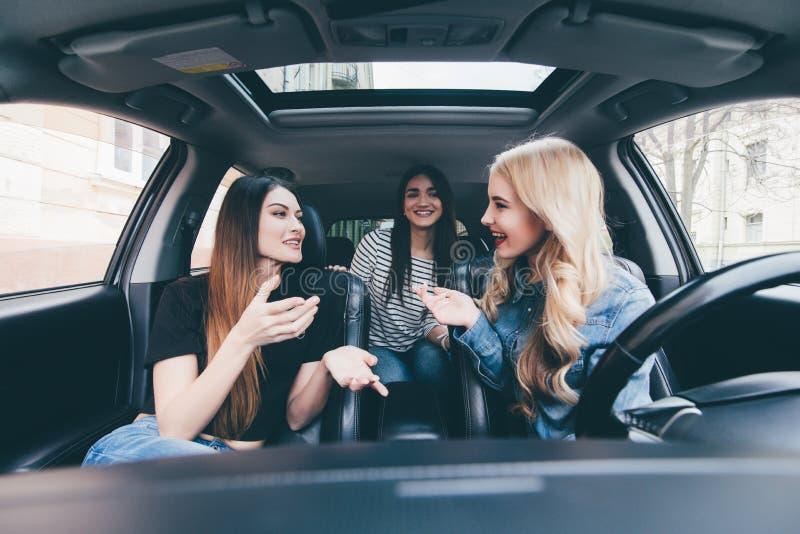 Tre härliga vänner för unga kvinnor har gyckel tillsammans i nolla-bilen, som de går på en vägtur tillsammans för deras sommarsem fotografering för bildbyråer