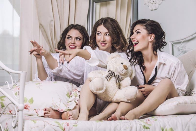 Tre härliga vänner för unga kvinnor som in pratar i sovrummet arkivfoto