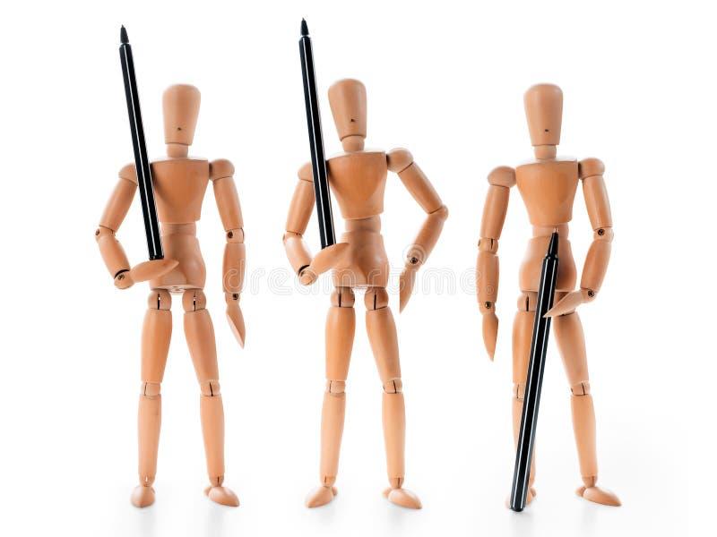 Tre hållande pennor för träskyltdockor som beväpnade vakter royaltyfri foto