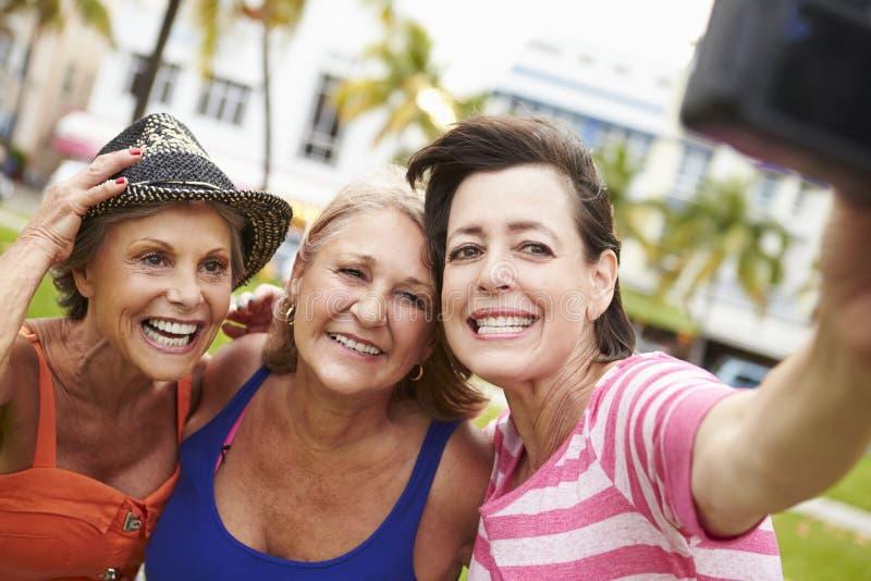 Tre höga kvinnliga vänner som tar Selfie parkerar in arkivbild