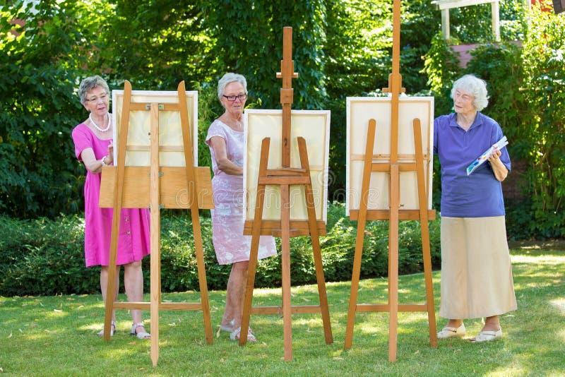 Tre höga kvinnor som målar på kanfas i trädgård eller att parkera under solig dag arkivfoton