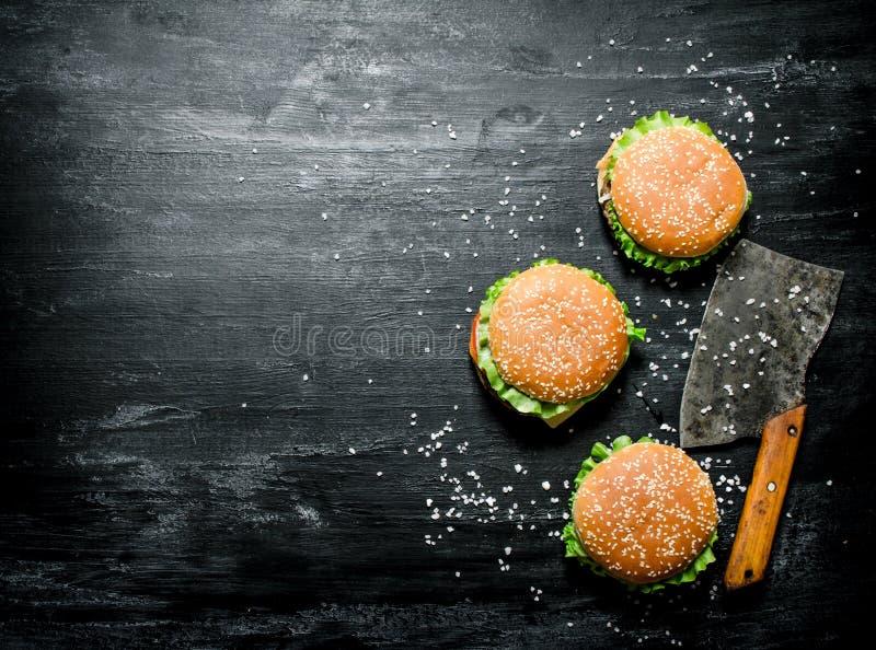 Tre hamburgare med en köttyxa På den svarta svart tavlan royaltyfria foton