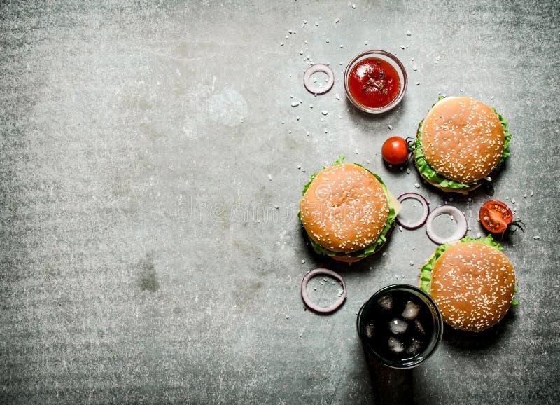 Tre hamburgare med en sodavatten på stentabellen royaltyfri bild