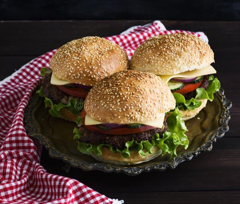 Tre hamburgare med ett kött hugger av, grönsaker och ost royaltyfri foto