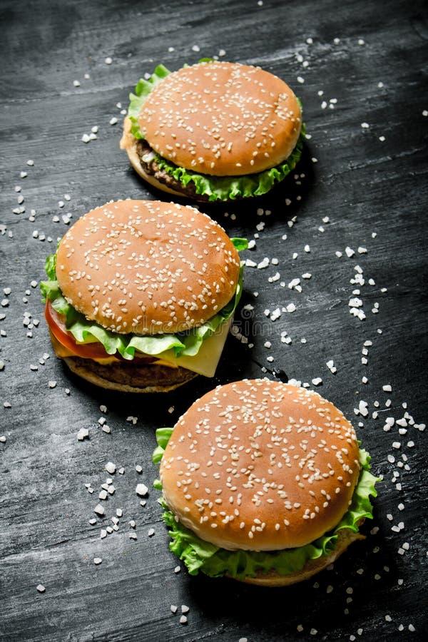Tre hamburgare med kött, ost och nya grönsaker arkivbilder