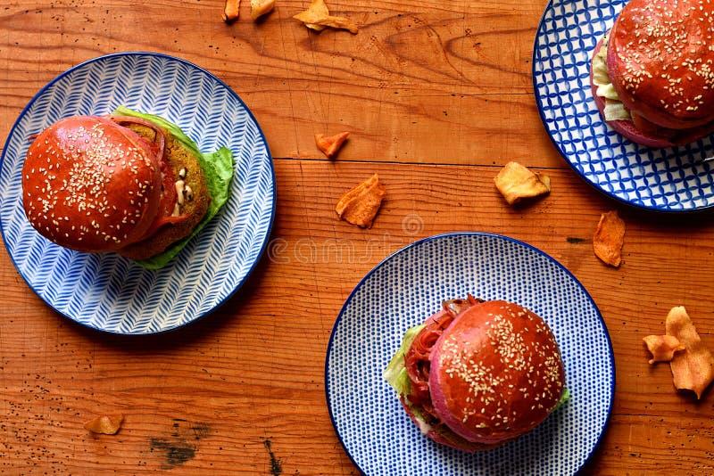 Tre hamburgare på blåa plattor royaltyfria foton