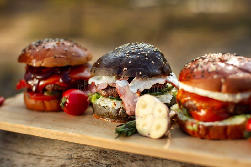 Tre hamburgare på en ljus träbrädeyttersida Clouse-up arkivfoto