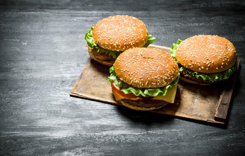 Tre hamburgare på ett träbräde arkivfoton
