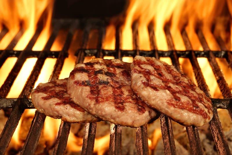 Tre hamburger bruniti casalinghi sulla griglia ardente calda del BBQ immagini stock