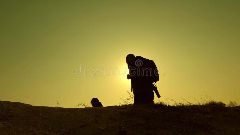 Tre handelsresande stiger ned från en kulle i strålar av sol en, efter annan har gått utöver horisont Teamwork av aff?rsfolk royaltyfria foton