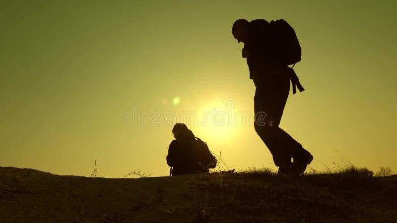 Tre handelsresande stiger ned från en kulle i strålar av sol en, efter annan har gått utöver horisont Teamwork av aff?rsfolk royaltyfri fotografi