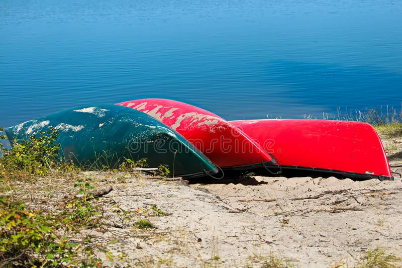 Tre hanno capovolto le canoe lungo una riva del lago fotografia stock libera da diritti