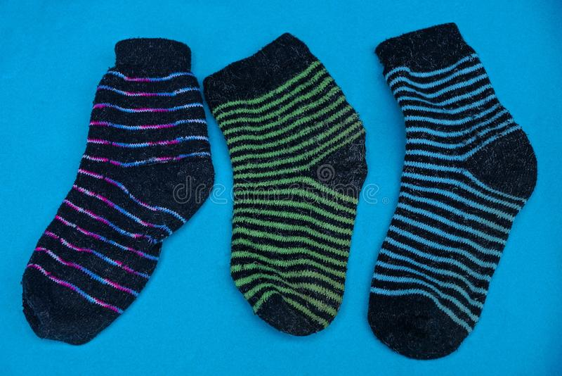 Tre hanno colorato i calzini di lana a strisce su una tavola blu immagine stock libera da diritti