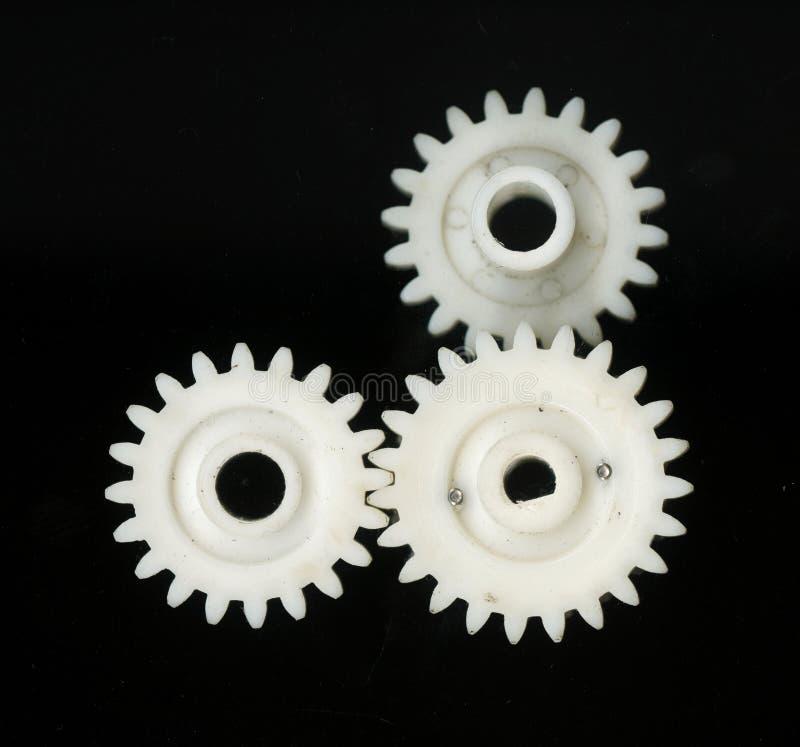 Tre hanno concatenato gli ingranaggi dentati di plastica bianchi delle dimensioni differenti su un fondo nero fotografia stock libera da diritti