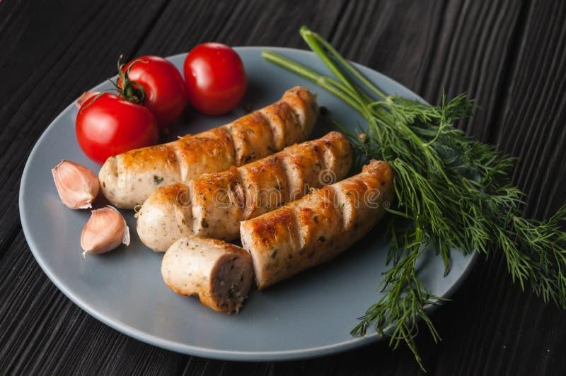 Tre hanno grigliato le salsiccie su un piatto grigio su un fondo nero di legno con i pomodori ciliegia, erbe, aglio fotografia stock libera da diritti