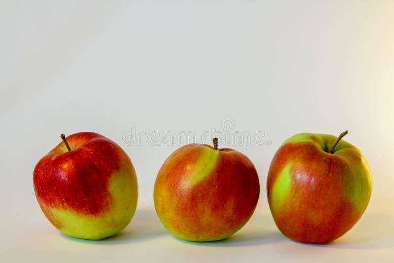 Tre hanno isolato le mele rosse e verdi sui precedenti bianchi fotografia stock libera da diritti