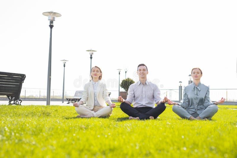Tre hanno sollecitato i capi corporativi che ritengono alleviati mentre praticavano l'yoga immagine stock