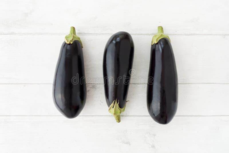 Tre hela aubergine på vit Wood bakgrund royaltyfri foto