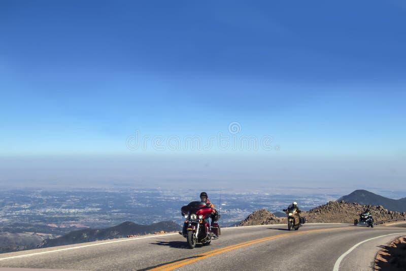 Tre helmeted motorcykelchaufförer rundar i rad en kurva ovanför trädlinjen på vägen upp Pikes Peak Colorado USA med a royaltyfri bild