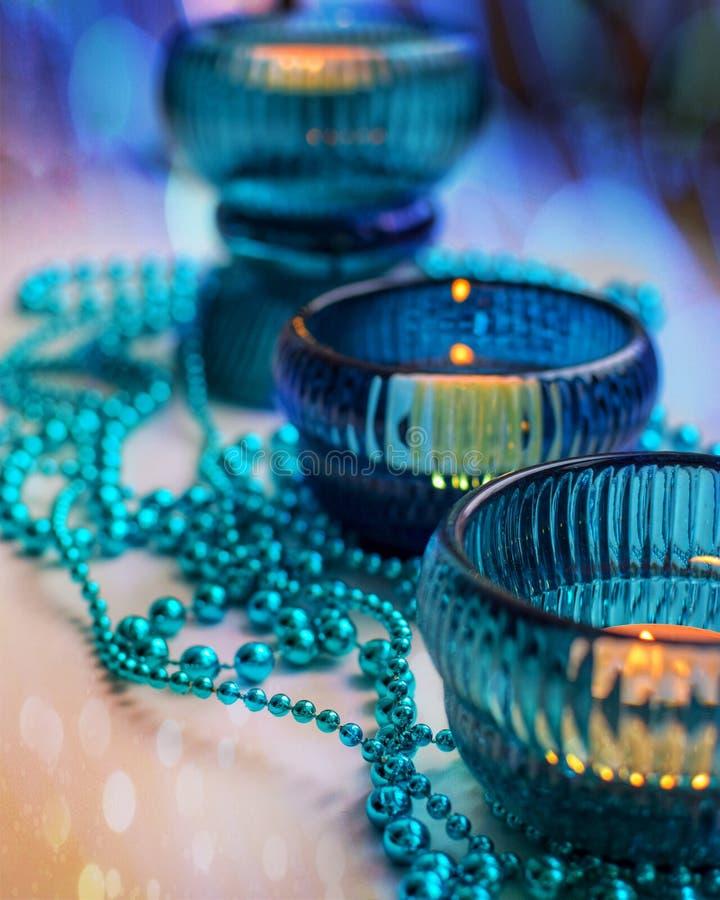 Tre hemtrevliga tända stearinljus i turkosljusstakar med julgirlanden i kalla färger med bokeheffekt royaltyfria foton