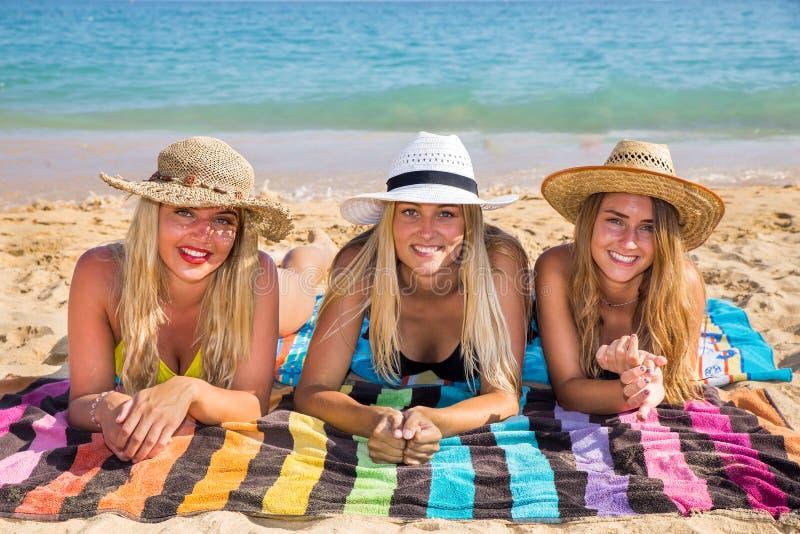 Tre holländska flickor som solbadar på stranden arkivbild