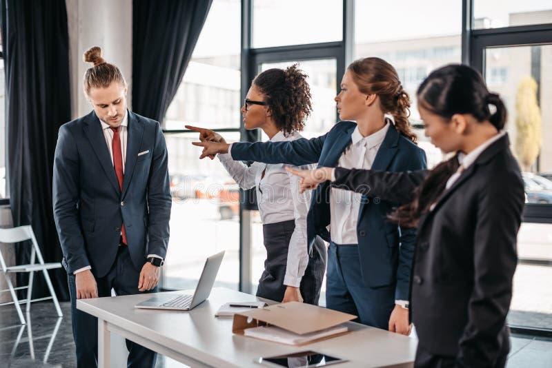 Tre ilskna unga affärskvinnor som i regeringsställning pekar med fingrar på den upprivna affärsmannen royaltyfria bilder